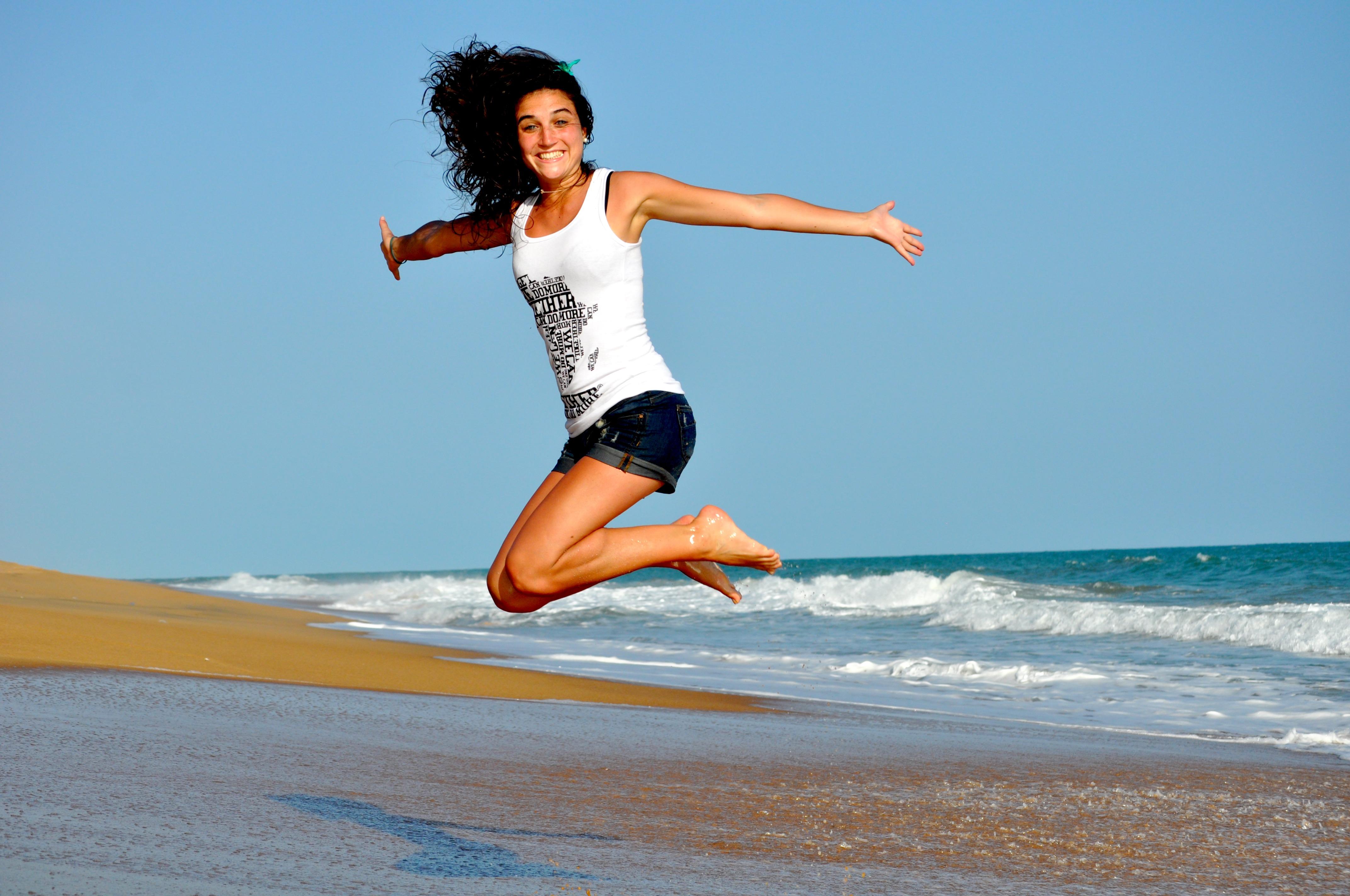 Junge Frau, die am Meer in die Luft springt