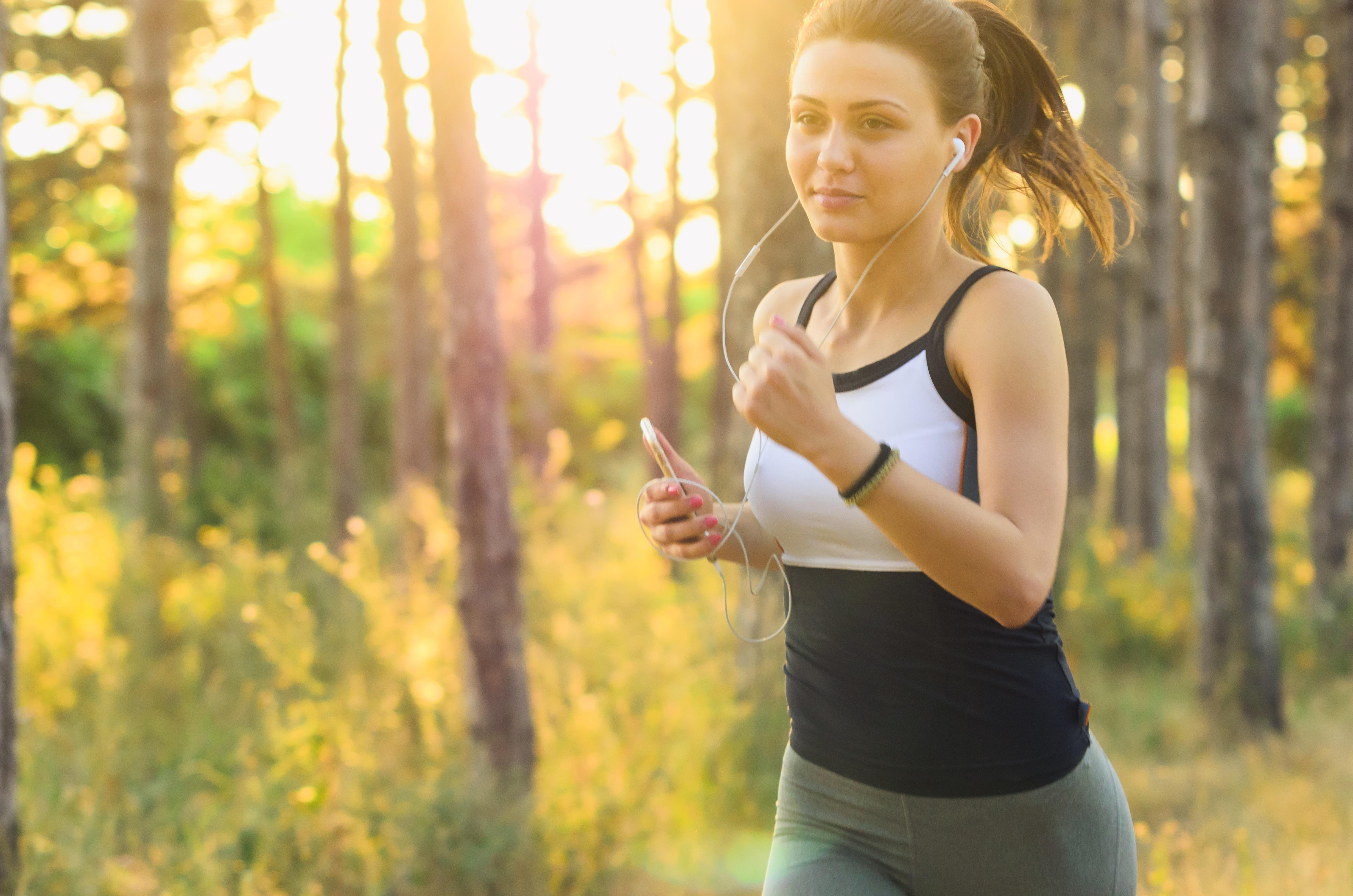Hilft Sport bei Migräne. Junge Frau die durch den Wald joggt